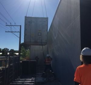 ICSSA refrigeration mechanics connecting a refrigerated shipping container before lowering it to its final position