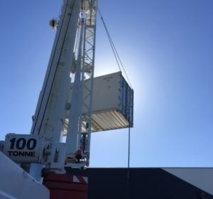 Installing a refrigerated shipping container using a crane for a supermarket in Frewville