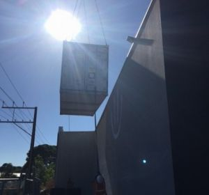 This photo shows how tight it was to install this refrigerated shipping container between power lines a perimeter fence and the wall of the building